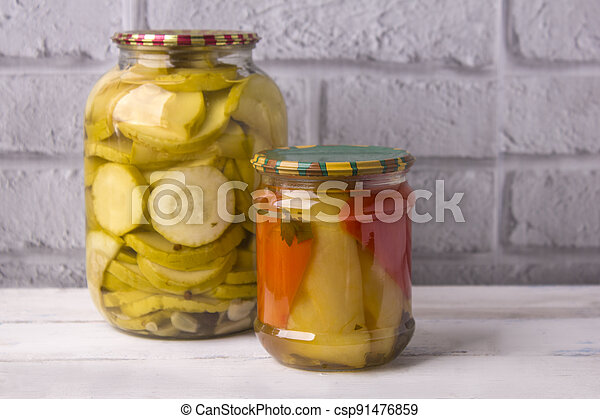 Jars of canned vegetables on a wooden background against a gray wall. Homemade vegetables for the winter - csp91476859
