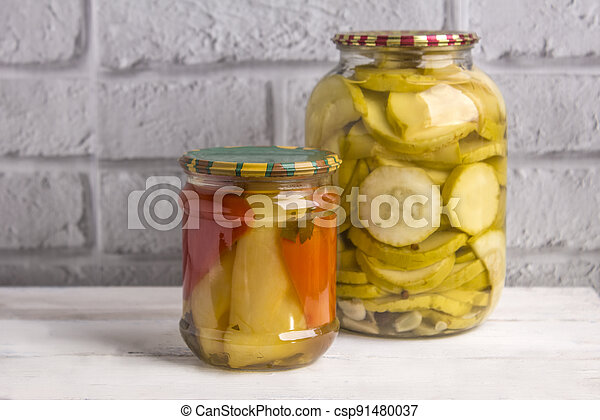 Jars of canned vegetables on a wooden background against a gray wall. Homemade vegetables for the winter - csp91480037