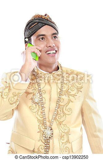 Hombre con traje de java tradicional usando teléfono móvil - csp13902250