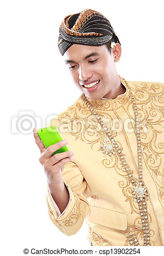 Hombre con traje de java tradicional usando teléfono móvil - csp13902254