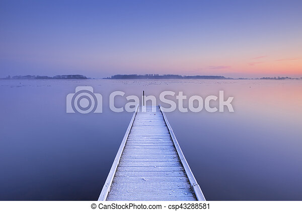 Jetty on a still lake in winter in The Netherlands - csp43288581