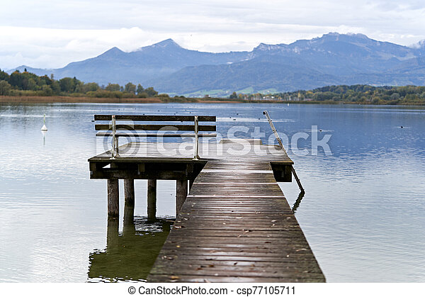 Jetty with a bench in a lake - csp77105711
