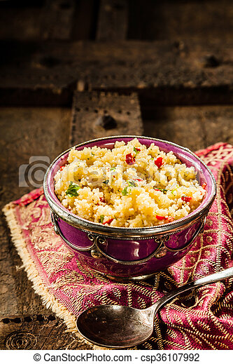 jeweled couscous in ornate bowl on wooden table high angle still