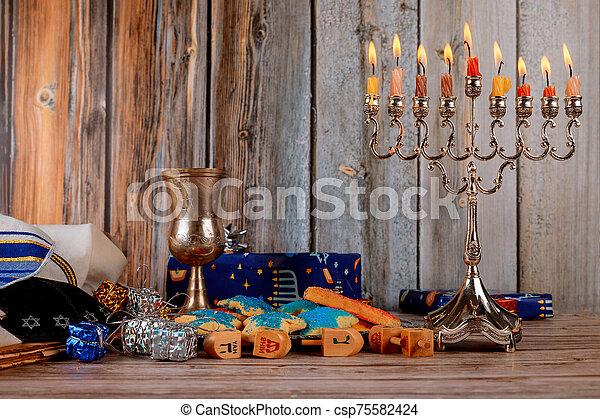 jewish holiday Hanukkah with menorah traditional Candelabra and wooden dreidels spinning - csp75582424