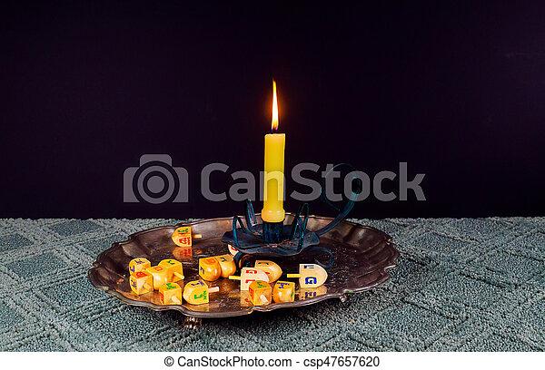 jewish holiday Hanukkahand wooden dreidels - csp47657620