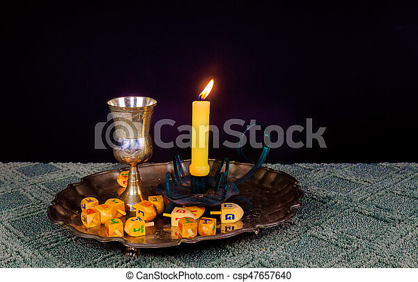 jewish holiday Hanukkahand wooden dreidels - csp47657640