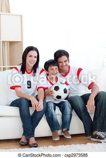 Jolly young family watching a football match  - csp2973588
