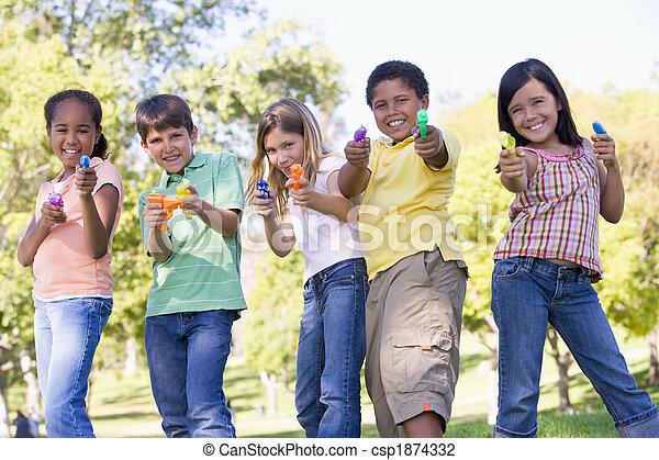 Cinco jóvenes amigos con armas de agua al aire libre sonriendo - csp1874332
