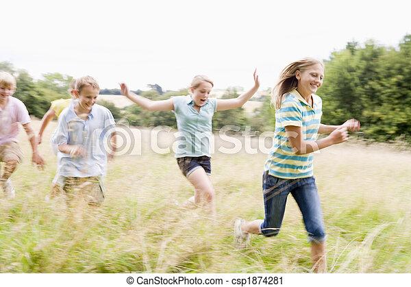 Cinco jóvenes amigos corriendo en un campo sonriendo - csp1874281