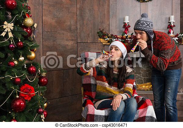 joven, fiesta de christmas, pareja, divertido, sombreros, soplar, silla, atractivo, silba, árbol, mecedor - csp43016471