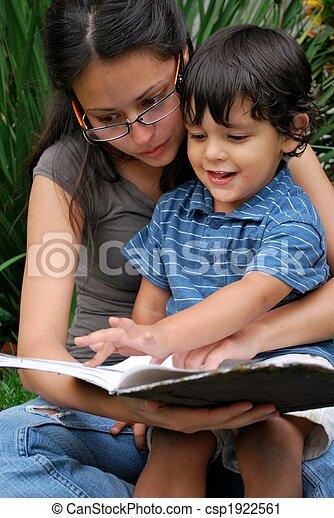 La joven madre hispana y su hijo leyendo juntos - csp1922561