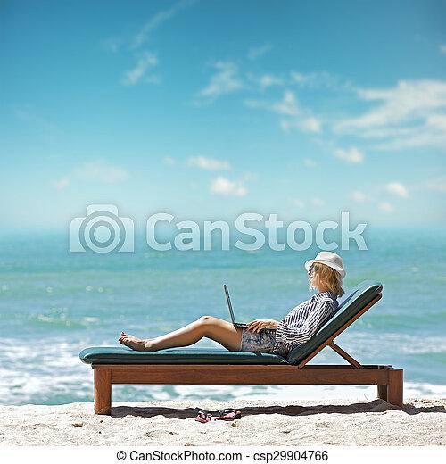 Mujer joven con portátil en la playa - csp29904766