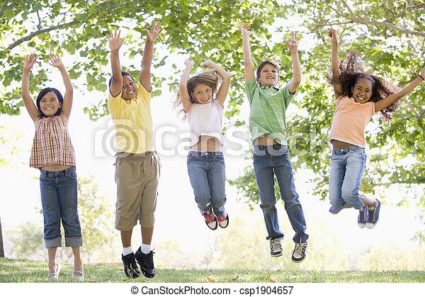 Cinco jóvenes amigos saltando al aire libre sonriendo - csp1904657