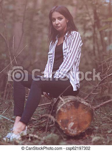 Una joven sentada en un tronco en el bosque. - csp62197302
