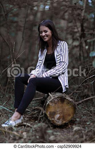 Una joven sentada en un tronco en el bosque. - csp52909924