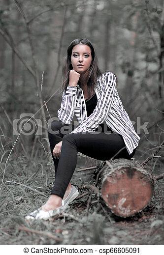 Una joven sentada en un tronco en el bosque. - csp66605091