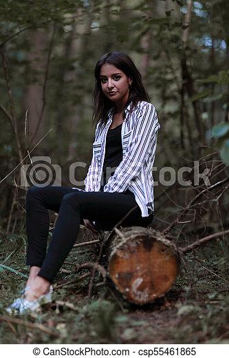 Una joven sentada en un tronco en el bosque. - csp55461865
