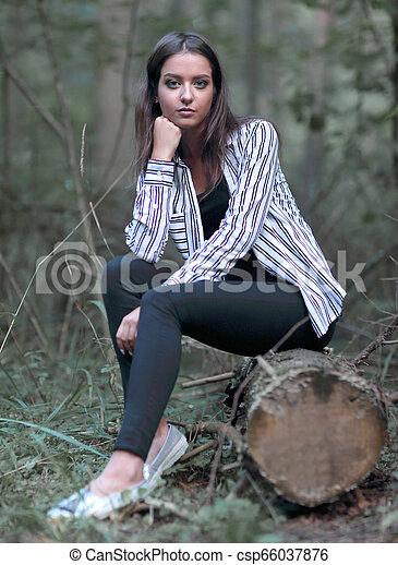 Una joven sentada en un tronco en el bosque. - csp66037876