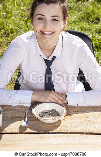 Joyful business woman sitting in front of a plate with money - csp47008706