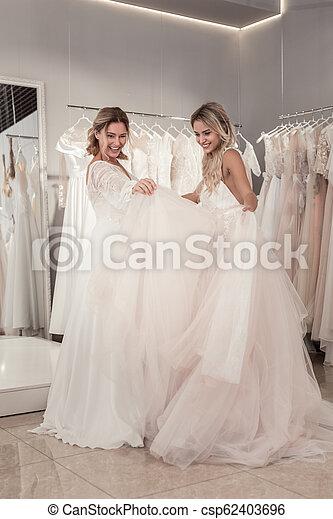 Joyful Delighted Women Trying On Wedding Dresses