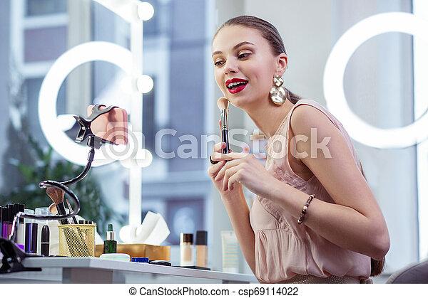Joyful pretty young woman showing makeup tutorial - csp69114022