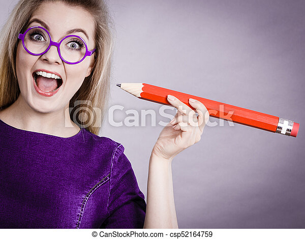 Joyful woman holds big pencil in hand - csp52164759