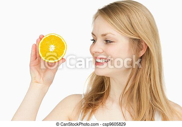 Joyful woman presenting an orange while looking at it - csp9605829