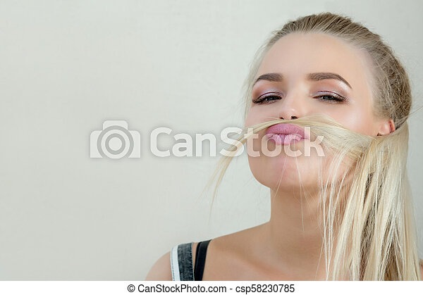 Joyful young blonde woman with perfect makeup posing over a white wall. Space for text - csp58230785