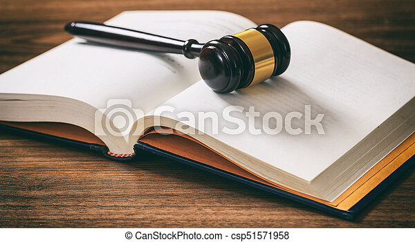 Judge or auction gavel on an open book, wooden desk - csp51571958