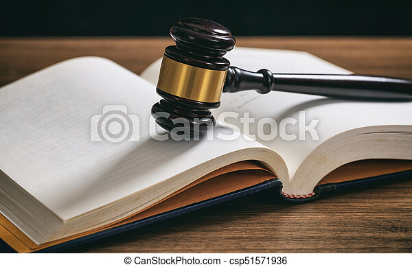 Judge or auction gavel on an open book, wooden desk - csp51571936