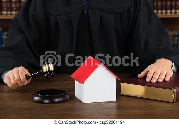 Judge With House Model Hitting Gavel At Desk - csp32201194