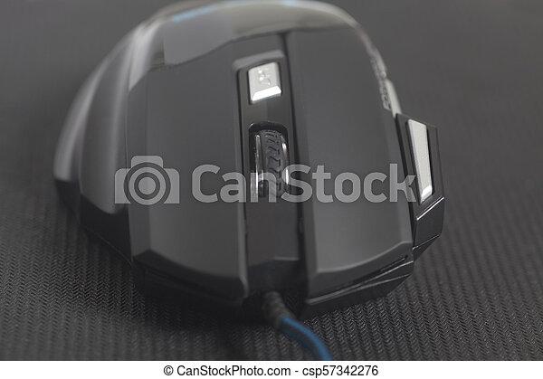 Un ratón de juego moderno en una almohadilla negra - csp57342276