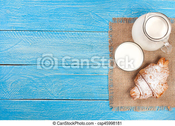 jug and glass of milk with croissants on a blue wooden background with copy space for your text. Top view - csp45998181