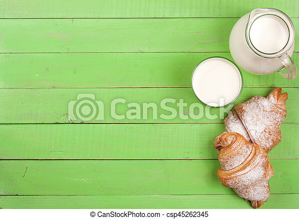 jug and glass of milk with croissants on a green wooden background with copy space for your text. Top view - csp45262345