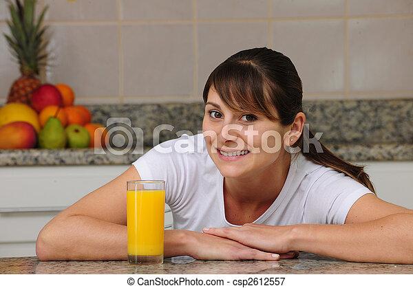 Mujer bebiendo jugo de fruta en la cocina - csp2612557