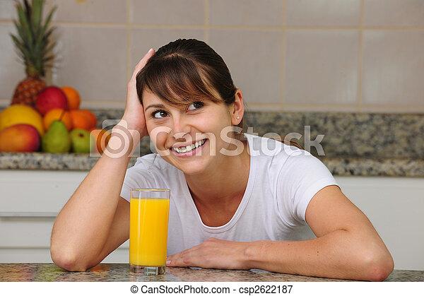 Mujer bebiendo jugo de fruta en la cocina - csp2622187
