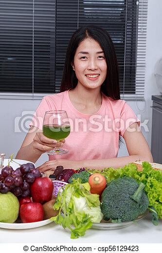 Mujer bebiendo jugo de vegetales en la cocina - csp56129423