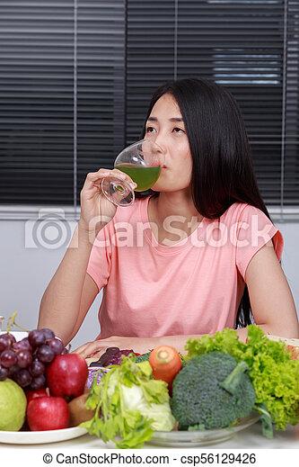 Mujer bebiendo jugo de vegetales en la cocina - csp56129426