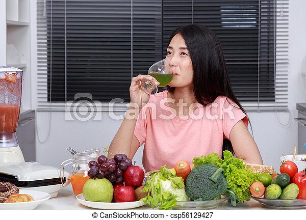 Mujer bebiendo jugo de vegetales en la cocina - csp56129427