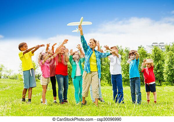 Un niño con un juguete de avión blanco y niños detrás - csp30096990