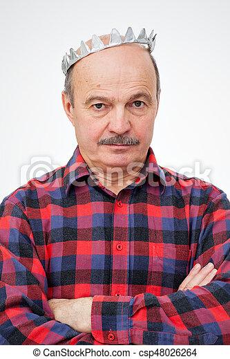 El anciano con una corona de juguete de papel se para con las manos dobladas en la cabeza. Mirada pensativa hacia adelante. - csp48026264