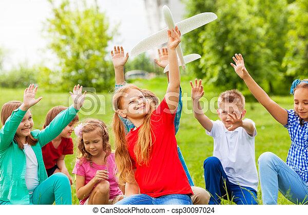 Una chica con un juguete y niños sentados detrás - csp30097024