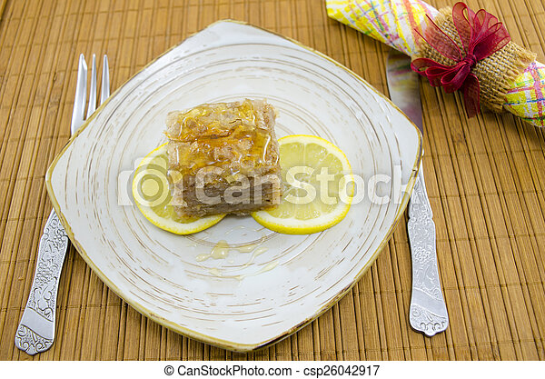 Juicy baklava on a plate decorated with lemon slices - csp26042917