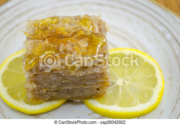 Juicy baklava on a plate decorated with lemon slices - csp26042922