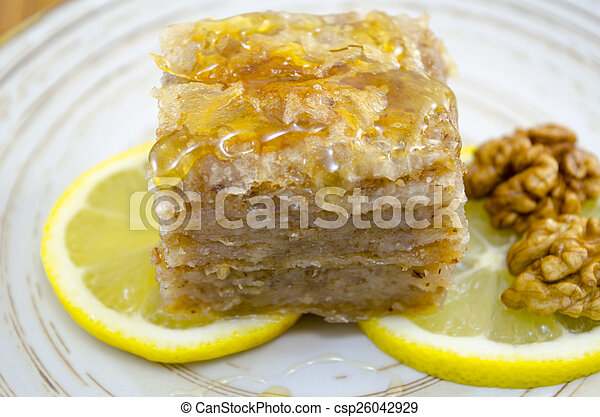 Juicy baklava on a plate decorated with lemon and walnuts - csp26042929
