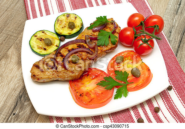 juicy grilled steak with vegetables on the plate on a wooden table - csp43090715