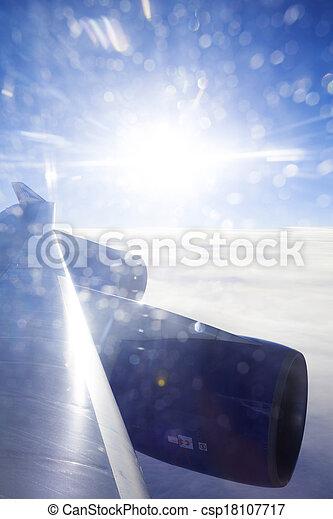 Jumbo Jet wing backlit by amazing sunset - csp18107717