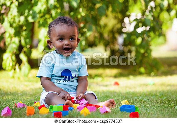 Der kleine afroamerikanische Junge, der im Gras spielt - csp9774507