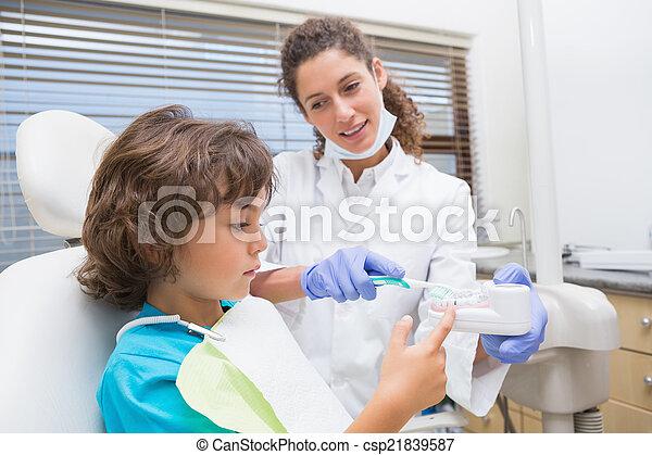 Kinderarzt zeigt dem kleinen Jungen, wie man seine Zähne putzt - csp21839587