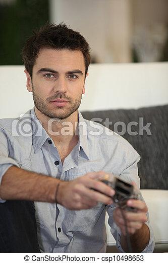 Ein junger Mann spielt allein Videospiele - csp10498653